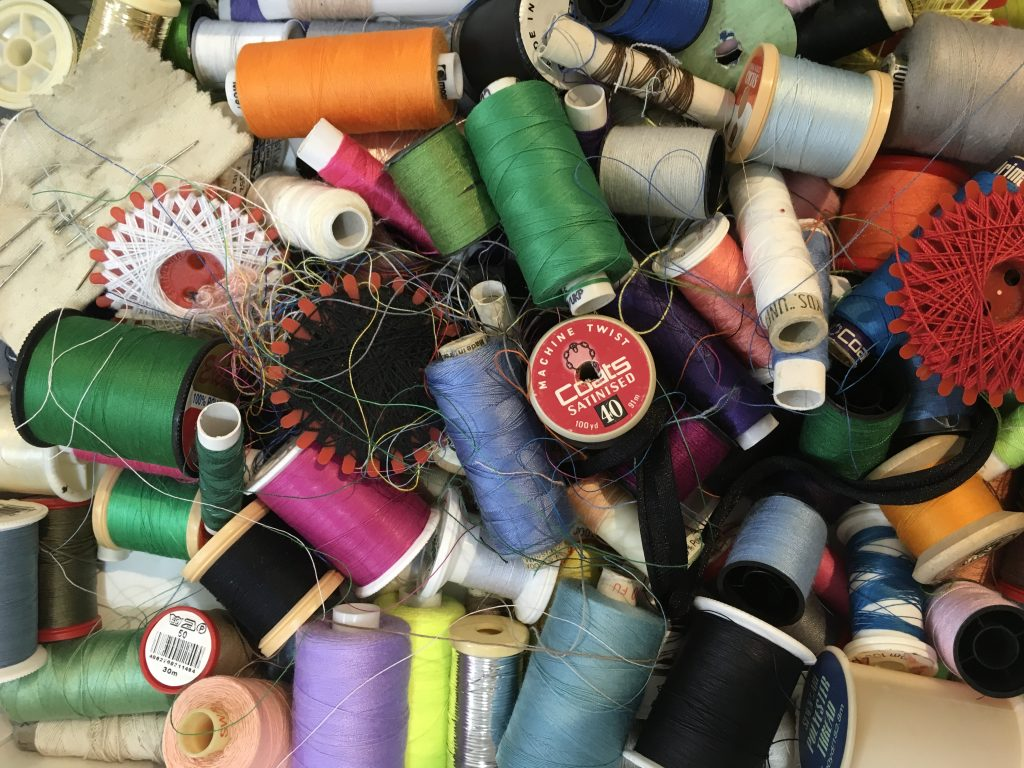 a box of sewing threads in bright colours mix of shapes and sizes
