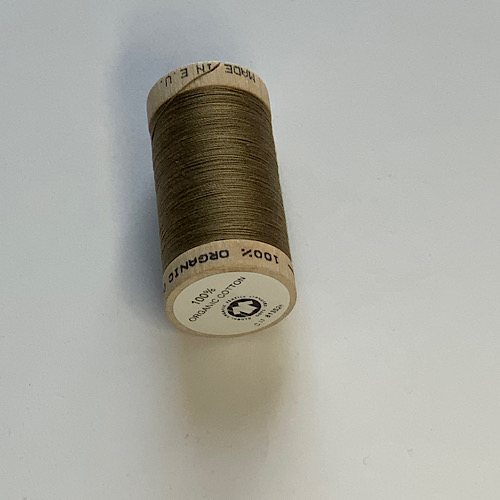 Olive green sewing thread on a wooden reel